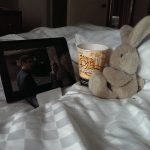 tablet, popcorn cup, stuffed animal on bed