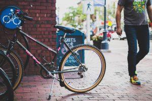 man walking past bicycle
