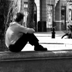 man sitting alone watching others