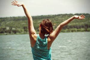 woman with arms raised in joy