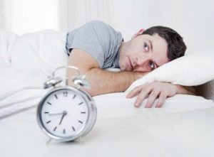 man awake in bed with alarm clock