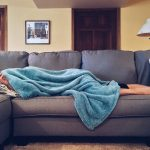 person sick under blanket on couch