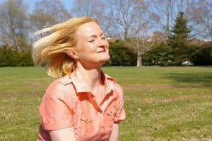 older woman in park with wind blowing back hair
