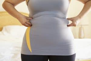 woman pinching fat rolls